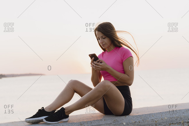 Athlete using mobile phone while sitting on concrete wall against sea