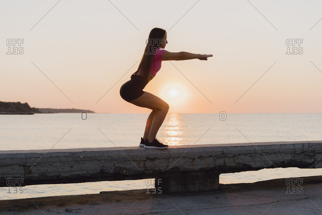 Sportswoman crouching while standing on concrete wall against sea