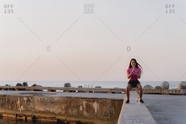 Young athlete exercising while standing on concrete wall against sea