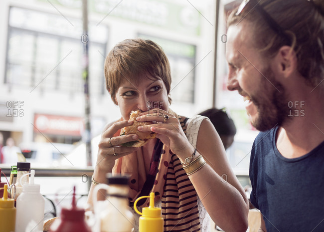 Young woman eating burger while sitting in cafe with mid adult man