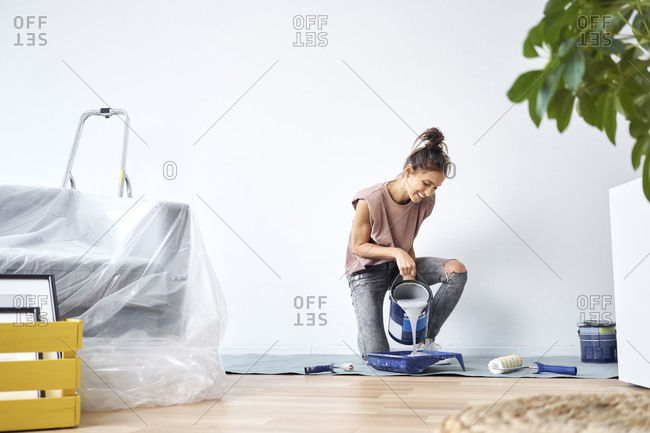 Smiling young woman pouring paint in paint tray while kneeling at home