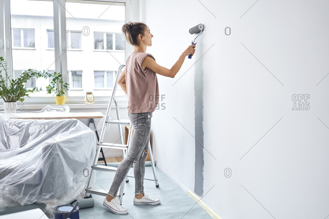 Young woman painting with paint roller on wall while standing at home