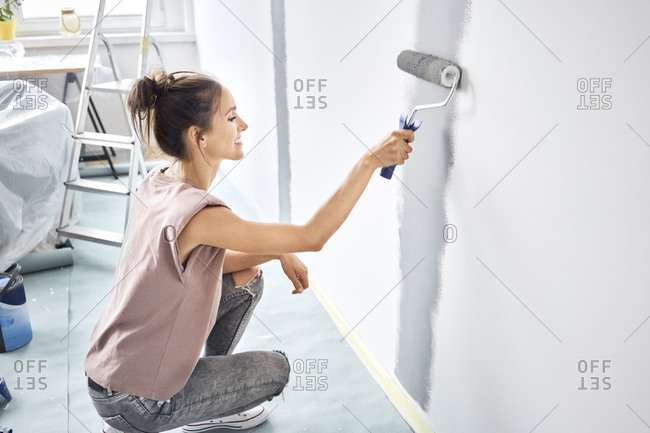 Smiling woman painting with paint roller on wall while crouching at home