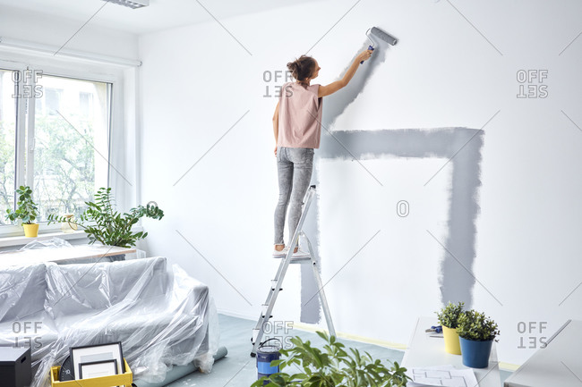 Young woman painting wall with pain roller while standing on ladder at home