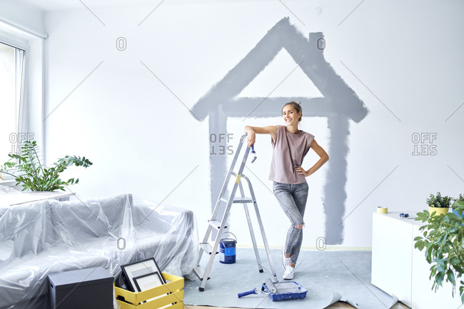 Smiling woman with hand on hip standing against house painted on wall at home