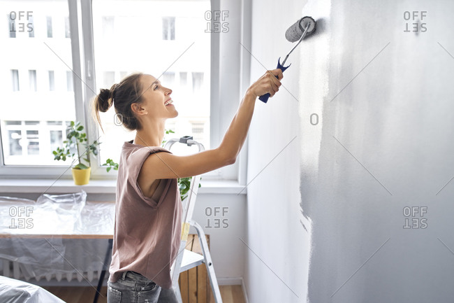 Smiling woman painting wall with paint roller while standing at home