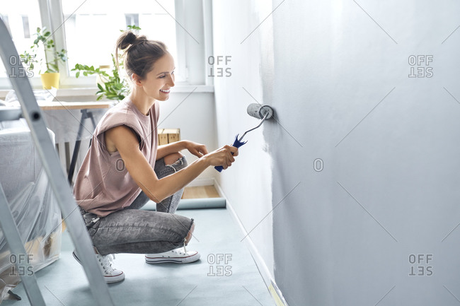 Young woman painting wall with paint roller while crouching at home