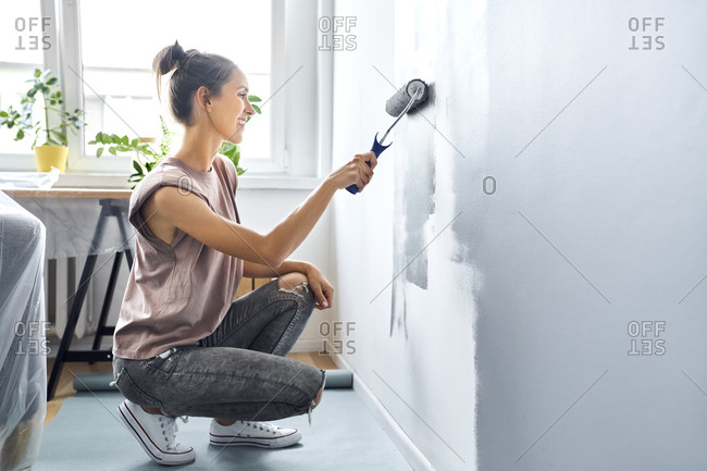 Woman smiling while painting wall at home