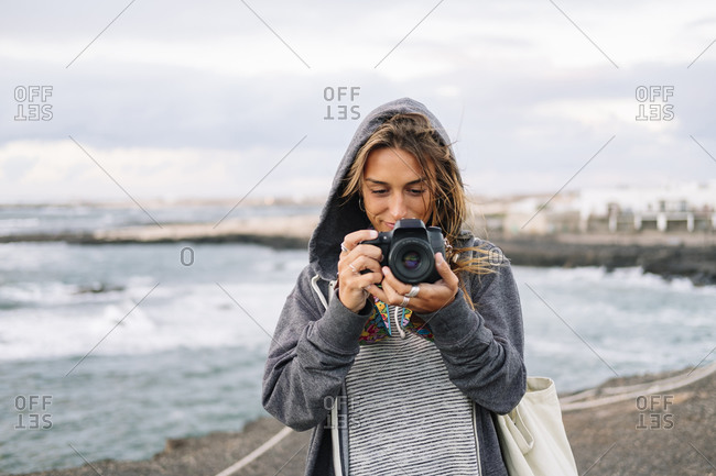 Young woman taking picture with camera while standing on beach
