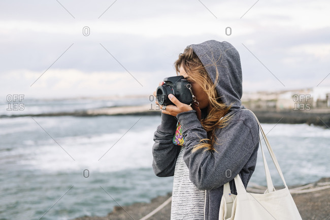 Woman taking picture with camera while standing on beach