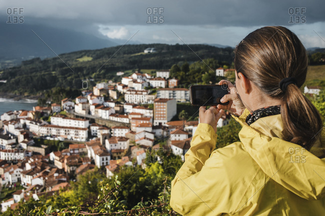 Rear view of woman photographing village through smart phone during vacations