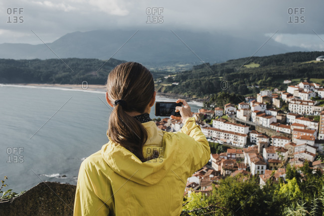 Rear view of woman photographing village through mobile phone during vacations