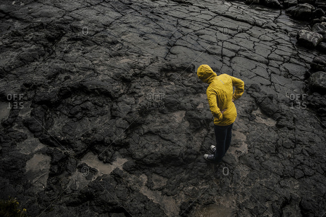 Drone shot of woman wearing raincoat while standing on rocky ground during rainy season