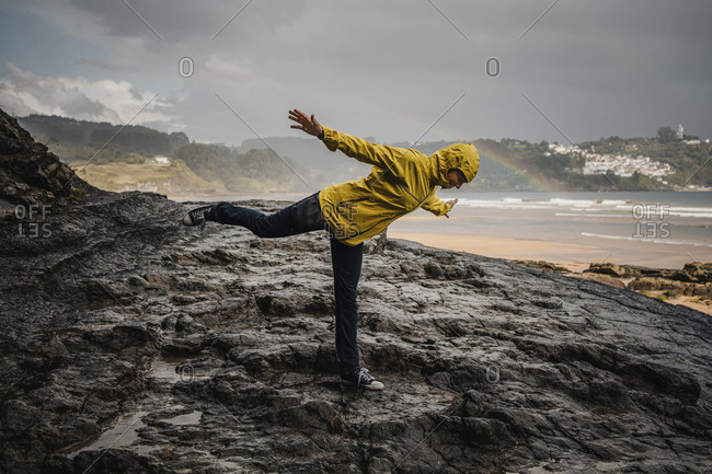 Playful woman wearing raincoat while standing on rocky ground during rainy season