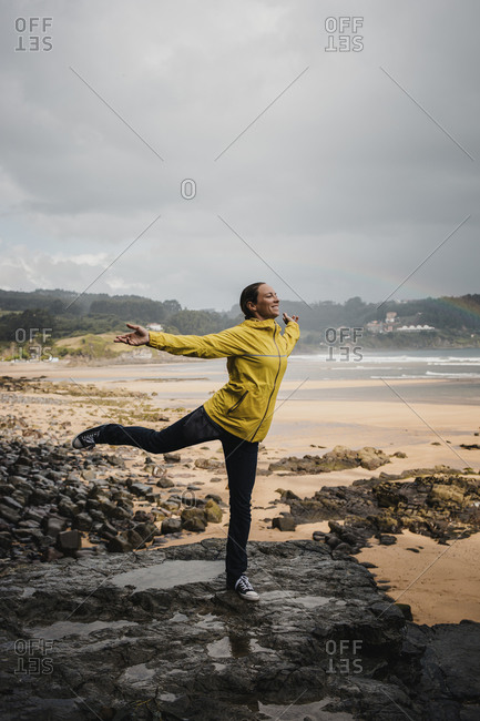 Playful woman in raincoat standing on one leg at beach during rainy season