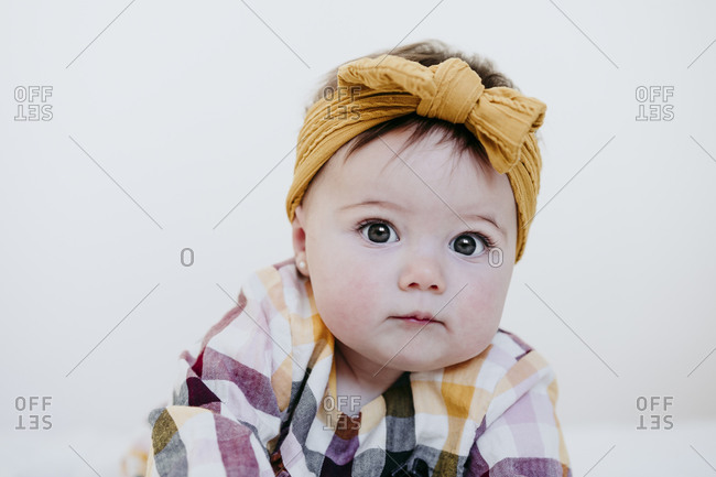 Baby girl wearing headband staring while lying on bed at home