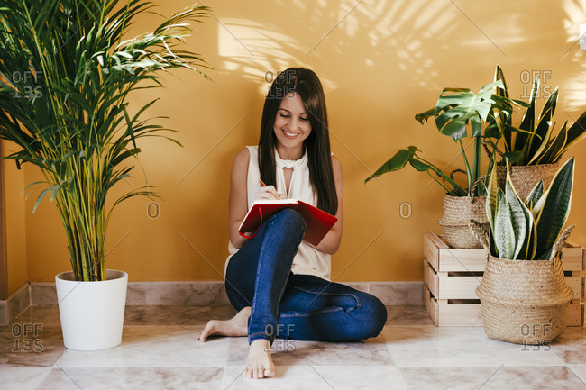 Woman writing in book while sitting on floor against yellow wall at home