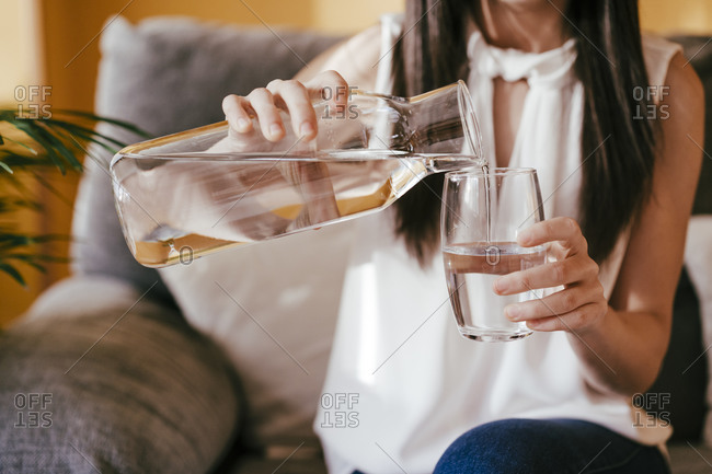 Woman pouring water from jar into drinking glass while sitting at home