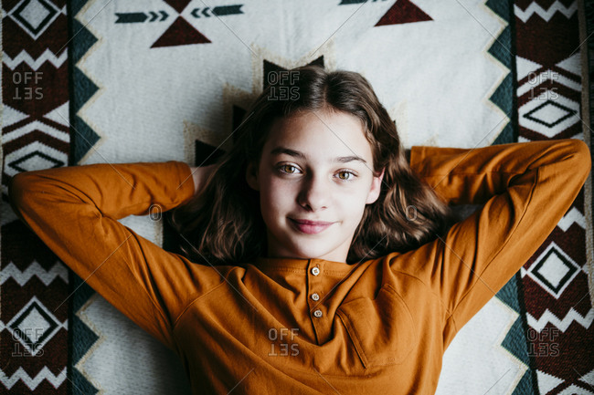 Smiling girl with hands behind head resting on blanket at home