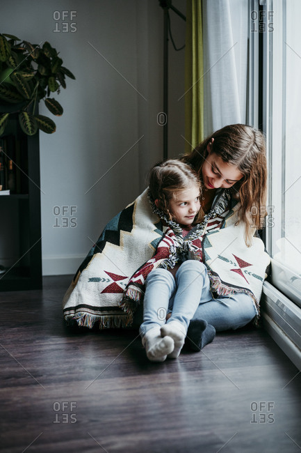 Girl sitting on sitter lap while sitting by window at home