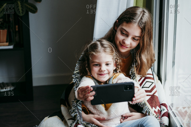 Girl taking selfie with sister while sitting by window at home