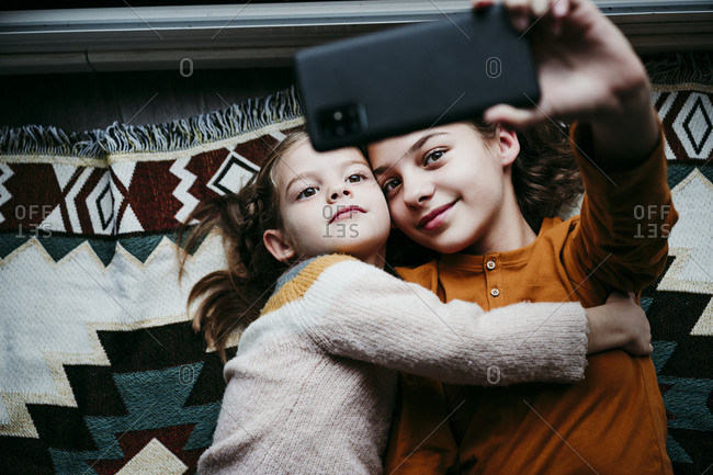 Girl embracing sister while taking selfie through mobile phone at home