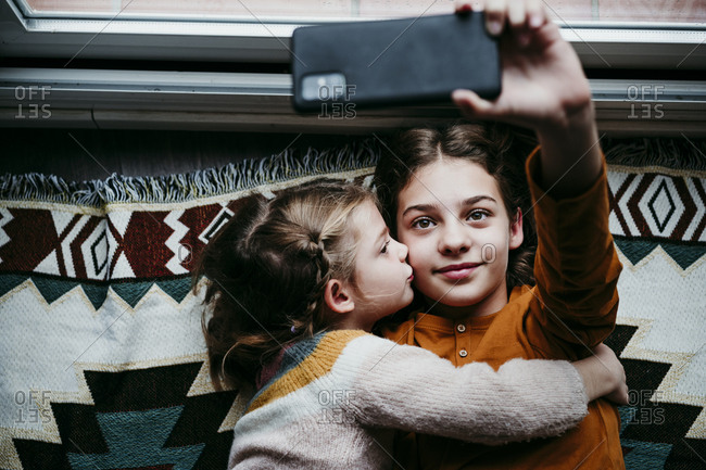 Girl kissing sister while taking selfie through mobile phone at home