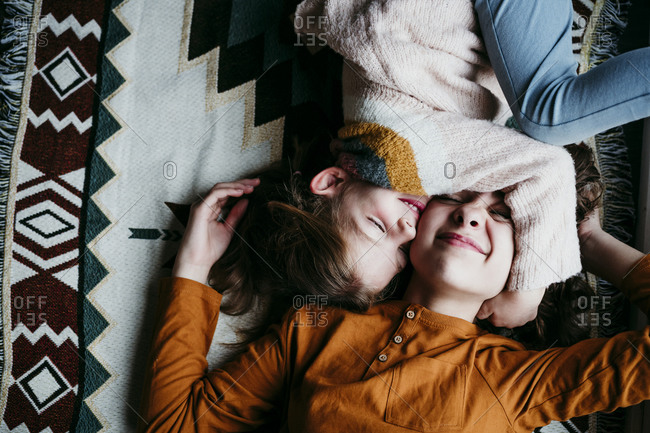 Girl embracing sister face while lying on blanket at home