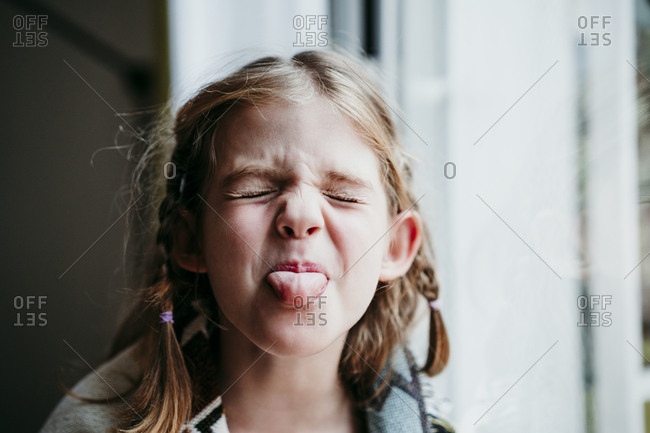 Blond girl sticking tongue out while standing by window at home