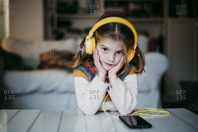Girl wearing headphones leaning on table with head in hands at home