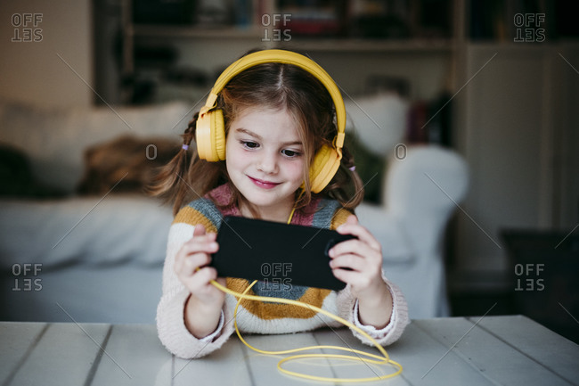 Smiling girl wearing headphones using mobile phone while standing at home
