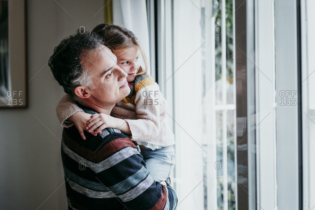 Father carrying daughter while standing by window at home