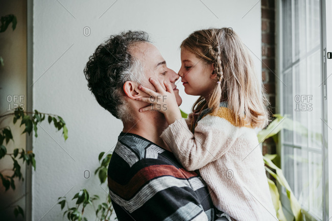 Daughter rubbing nose with father while standing by window at home