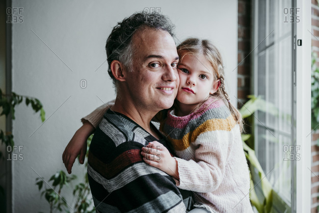 Smiling father carrying daughter while standing by window at home