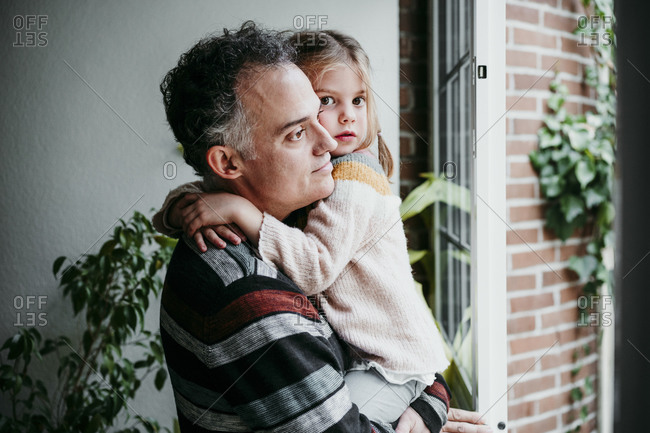 Father with daughter looking through window while standing at home