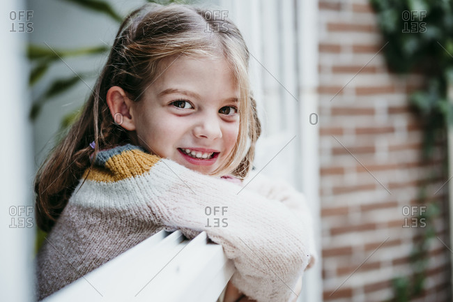 Smiling girl leaning on window while standing at home