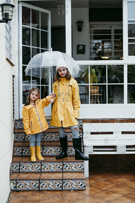 Sisters wearing raincoat holding umbrella while standing on staircase