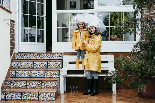 Smiling sister holding umbrella by sister standing on bench against home