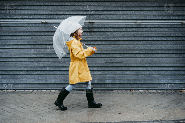 Girl wearing raincoat and jump boot holding umbrella while walking on sidewalk