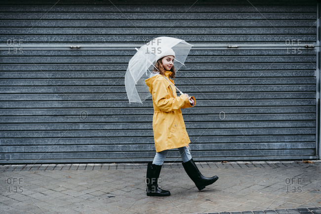 Girl wearing raincoat and jump boot walking on sidewalk outdoors