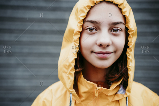 Smiling girl wearing raincoat standing outdoors