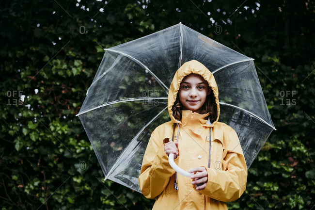 Girl wearing raincoat holding umbrella while standing against leaf wall