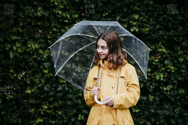 Girl wearing raincoat looking away while standing against leaf wall