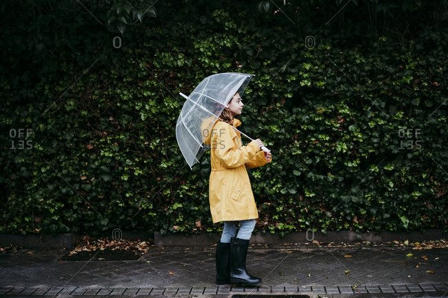 Girl wearing raincoat holding umbrella while walking against leaf wall in city