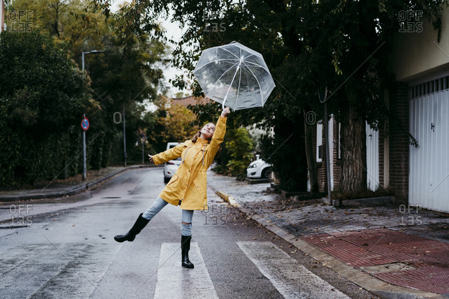Girl wearing raincoat dancing with umbrella while standing on road in city