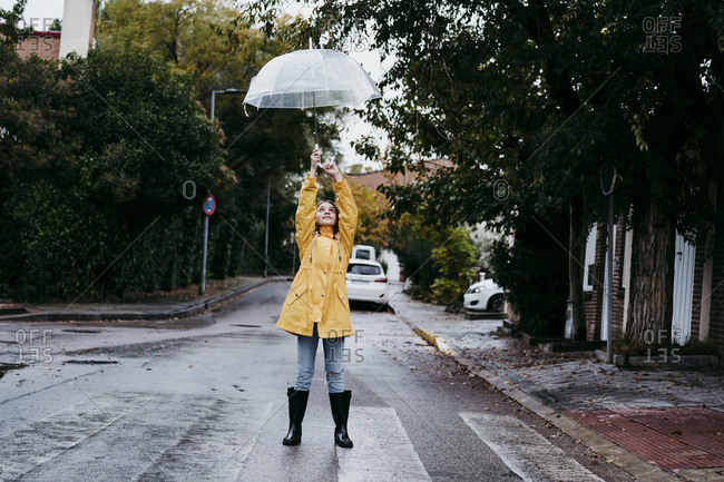 Girl wearing raincoat and jump boot standing on road in city
