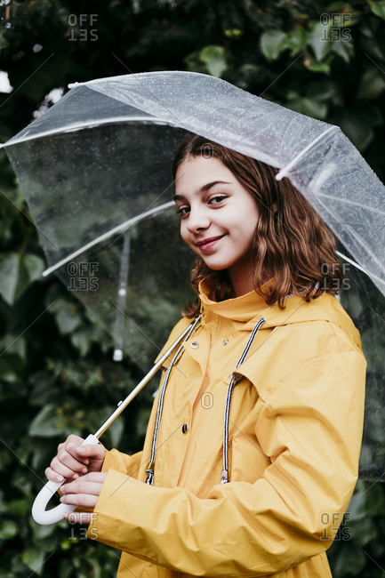Smiling girl in raincoat holding camera while standing against leaf wall