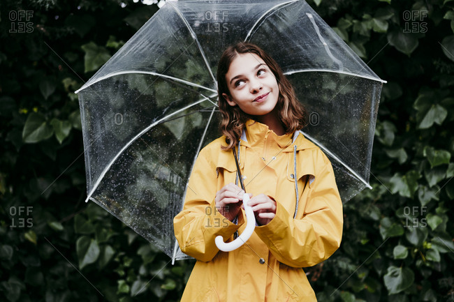 Thoughtful girl smiling while holding umbrella against leaf wall