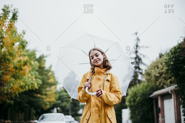 Smiling girl in raincoat holding umbrella while standing in city