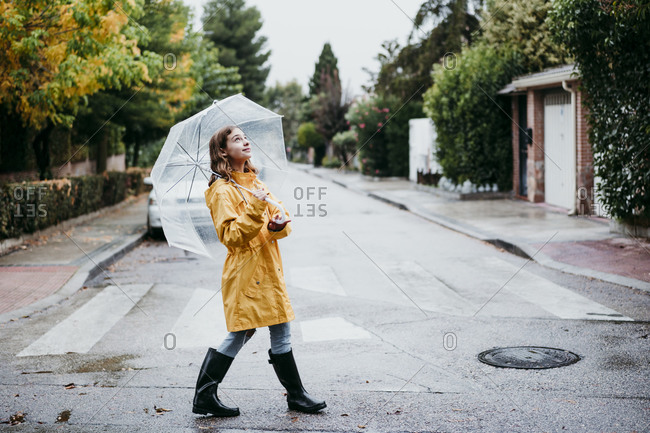 Smiling girl in raincoat holding umbrella while walking on road in city